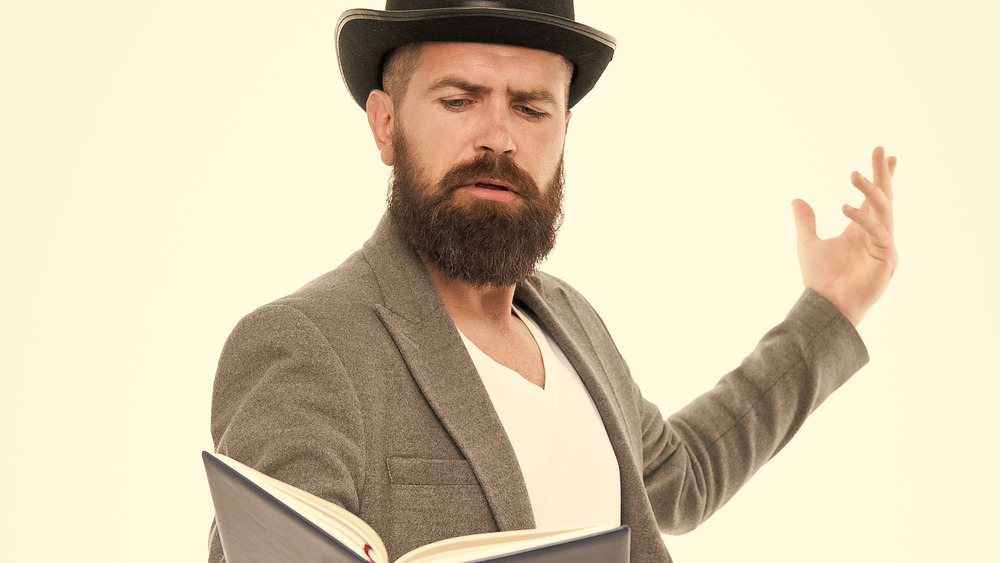 A man acts out something he's reading in a book