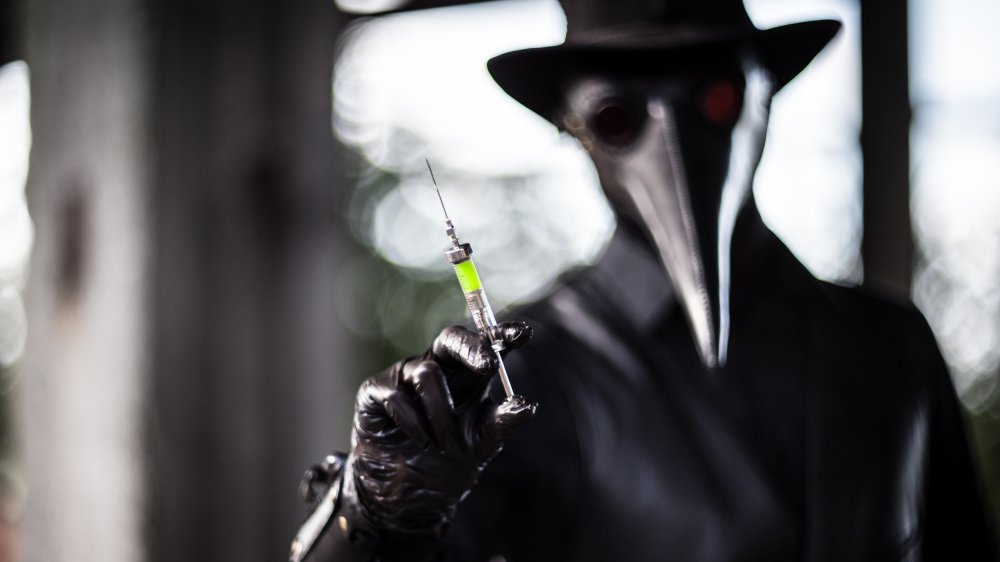 Plague doctor shows a syringe with a poisonous green liquid.