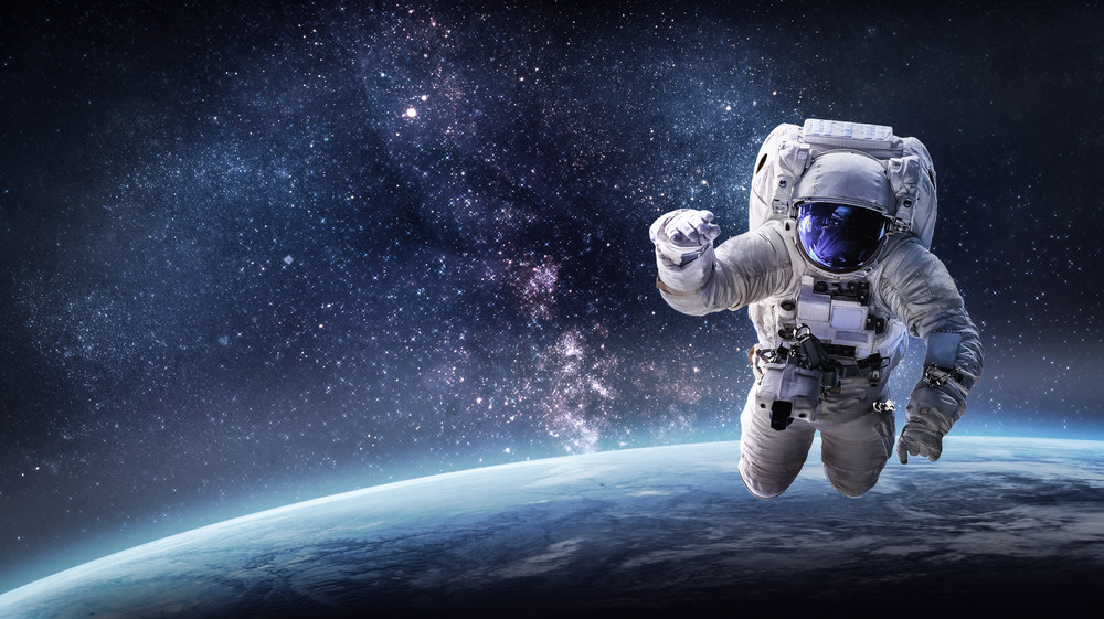 Astronaut floating in space above planet earth