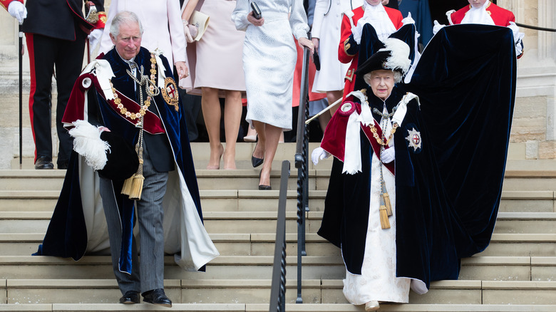 Queen Elizabeth and Prince Charles walking down steps