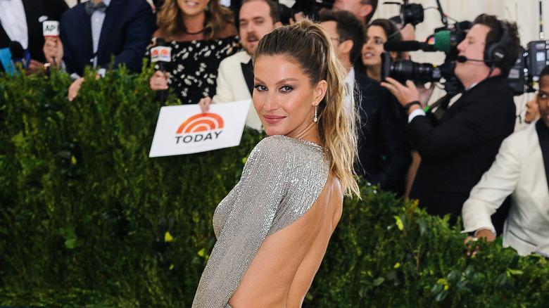 Giselle Bundchen looking over her left shoulder in a backless silver dress