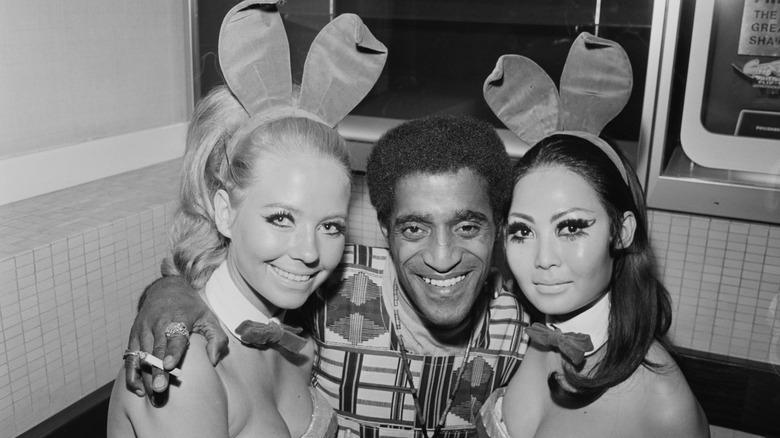 Sammy David Jr. smiling between two Playboy bunnies