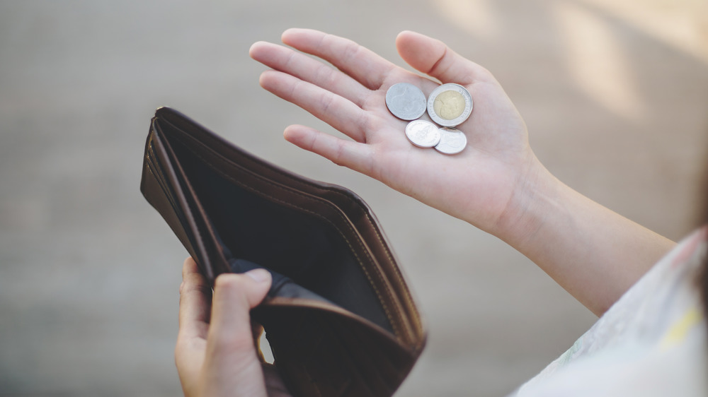 Woman with an empty wallet and a few coins