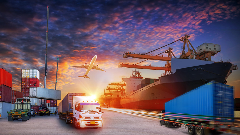 busy port with trucks, ships, and containers, plane overhead