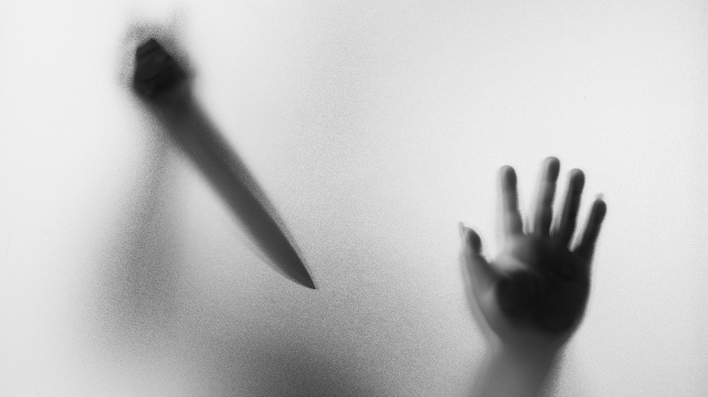 Hand on glass outline of knife