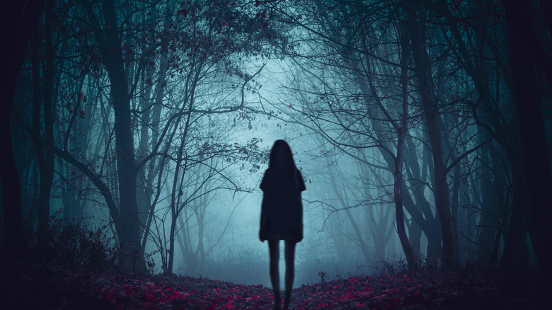woman in a spooky forest