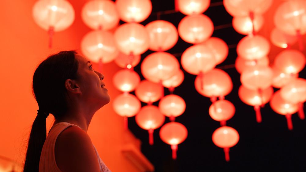 woman looking at red lanterns