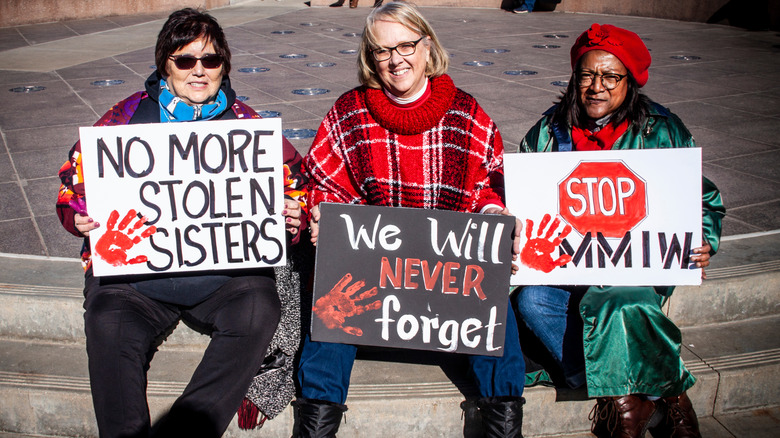 women holding MMIW protest signs
