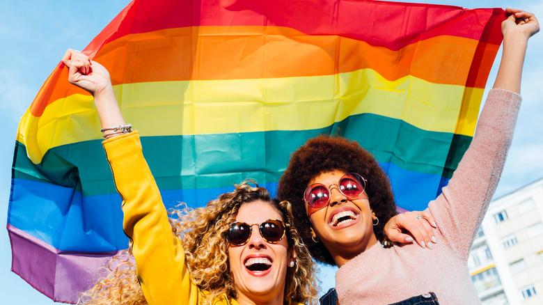 women flying LGBTQ+ pride flag