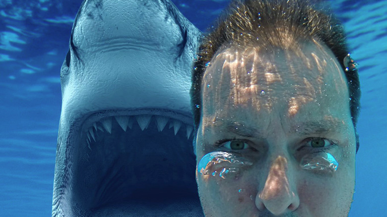акула позади человека, делающего селфи