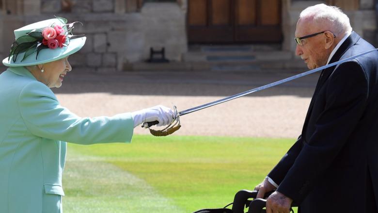 Queen Elizabeth putting a sword on a man's shoulder