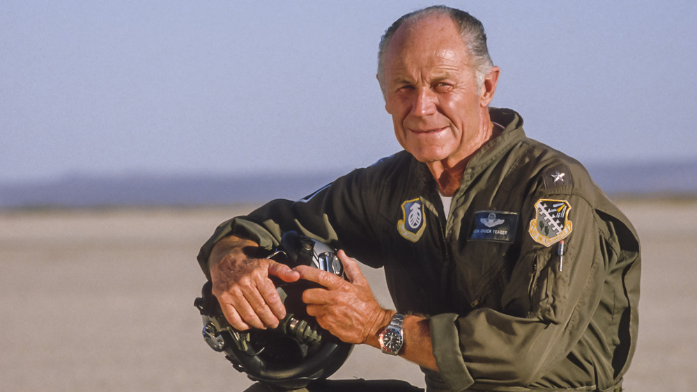 A picture of Chuck Yeager kneeling in an airfield around the 1980s.
