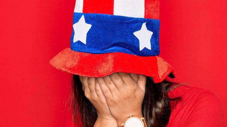 Patriotic woman hiding her face