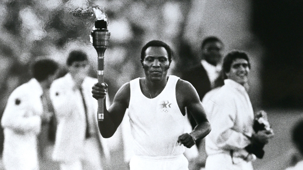 Former gold medalist in the decathlon, Rafer Johnson carries the torch on the final leg to to start the 1984 Summer Olympics at the Los Angeles Memorial Coliseum, Los Angeles, California.