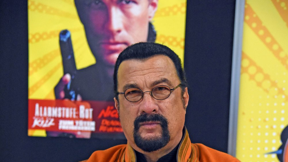 Steven Seagal in front of a poster of Steven Seagal