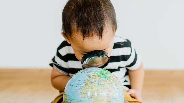 Toddler examines a globe