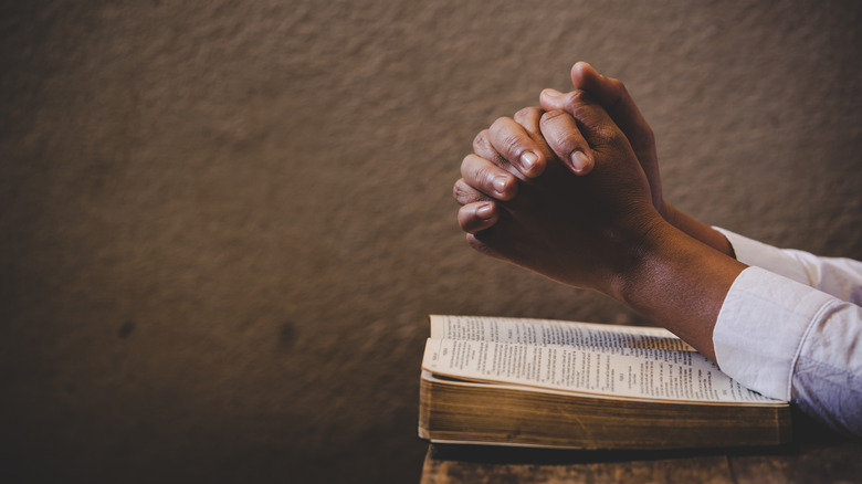 clasped hands over Bible