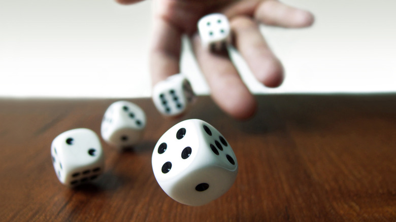 a hand throwing dice