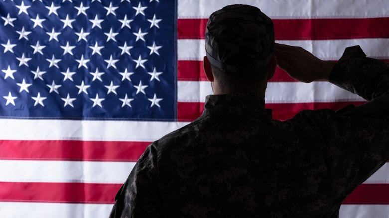 Solider salutes American flag