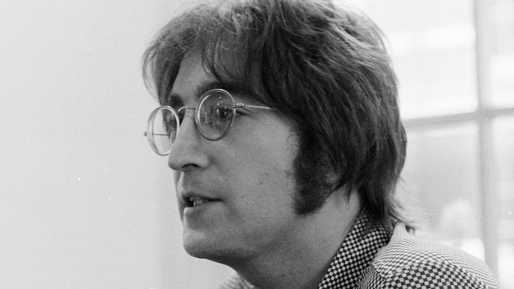 A black-and-white profile shot of John Lennon