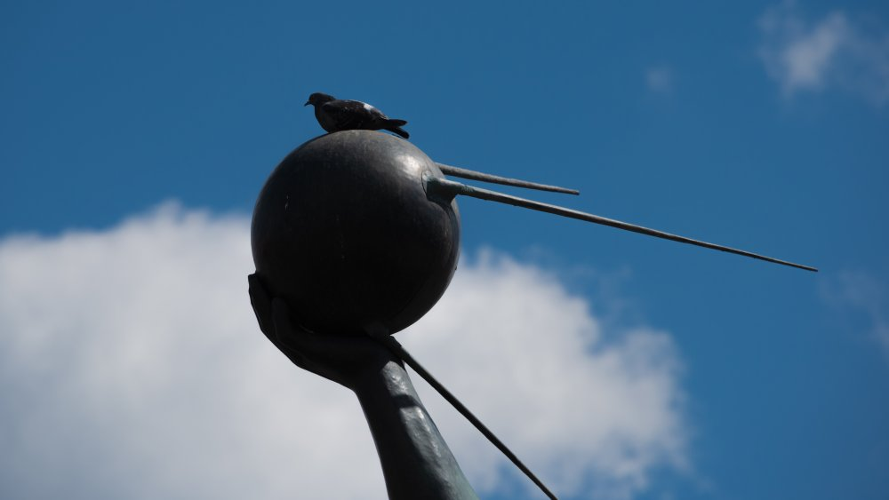 A statue of a person holding the Sputnik satellite.
