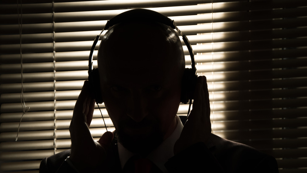 The silhouette of a secret agent gives directives into a headset