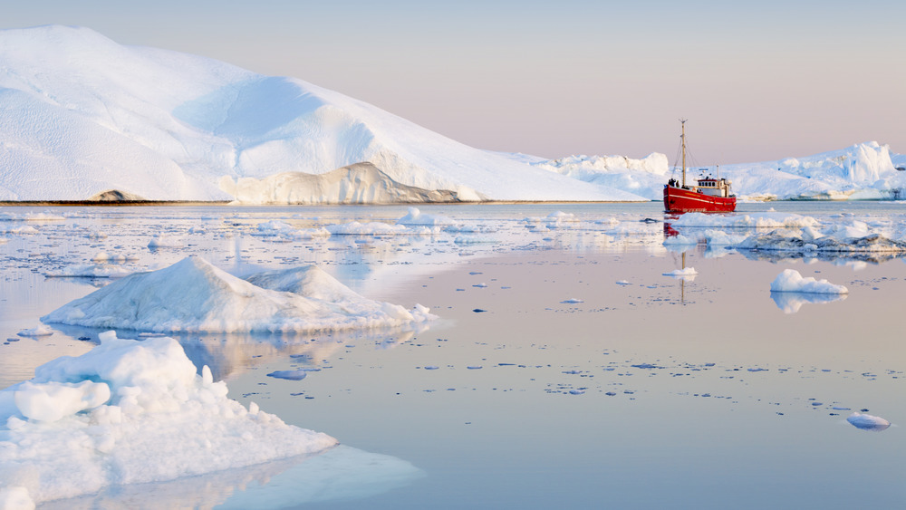A photograph of a boat in the frozen Arctic waters near the North Pole.