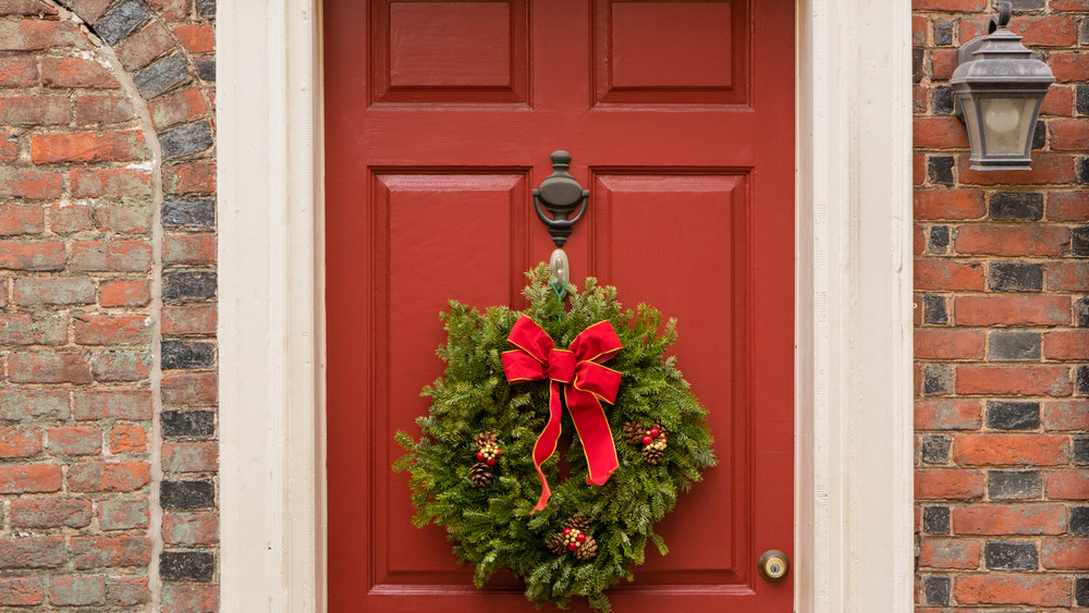 Colonial red doorway in historic Elfreth's Alley in Philadelphia with pediment and Christmas wreath.