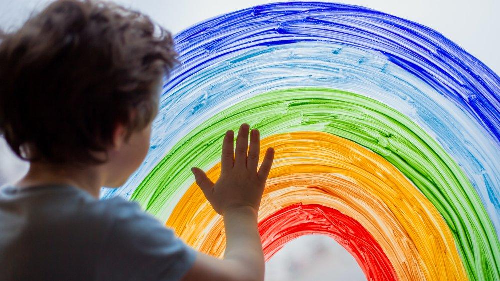 Kid painting a rainbow