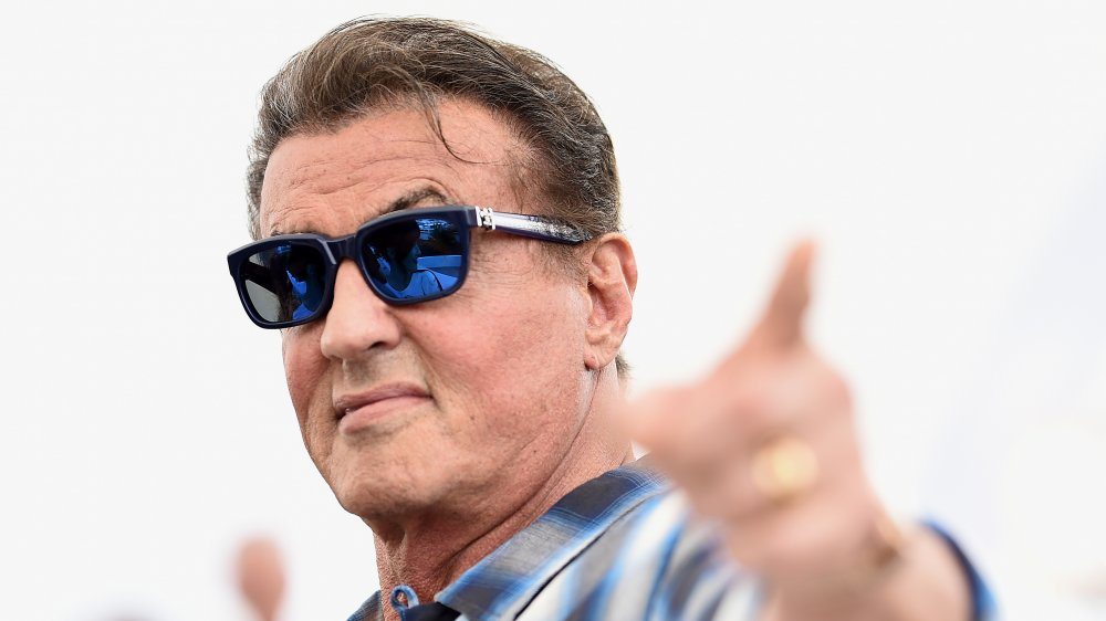Sylvester Stallone wears some sunglasses and points at the camera