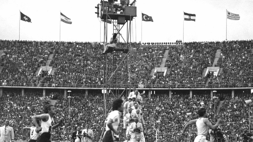 A photograph of runners at the 1936 Summer Olympics, with national flags at the top of the stadium.