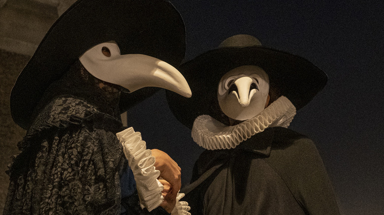 couple wearing plague doctor costumes