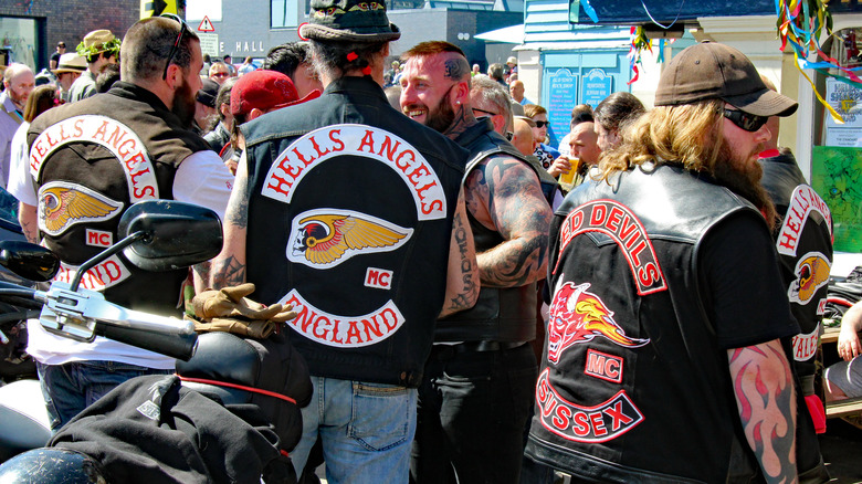 Three Hells Angels from back with patches on vests