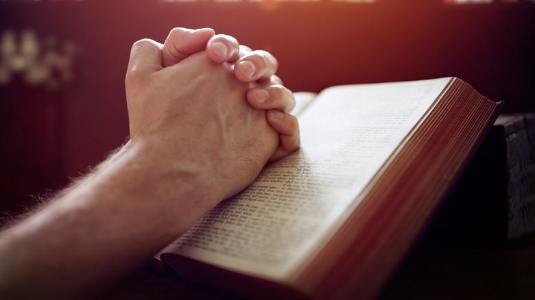 Man's hands clasped over an open bible.