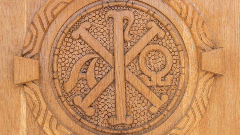 Wooden carving of the chi ro and alpha and omega