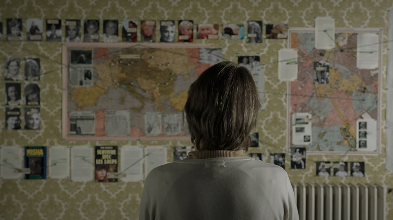 woman looking at investigatory material pinned to wall