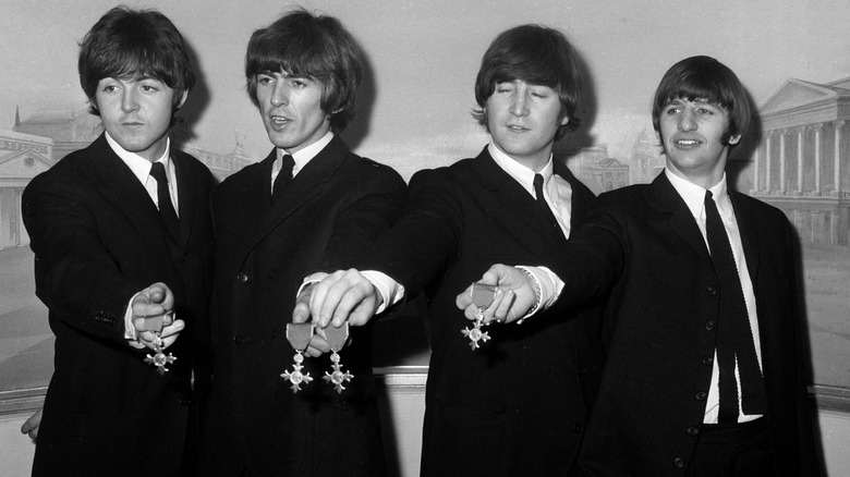 Beatles posing with MBE medals