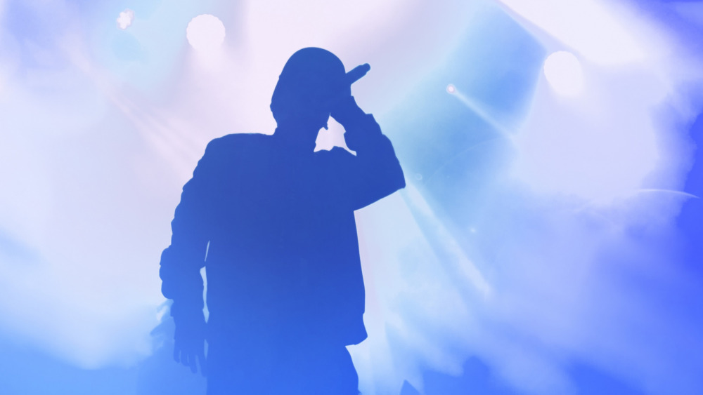 Image of a singer holding a microphone on stage.
