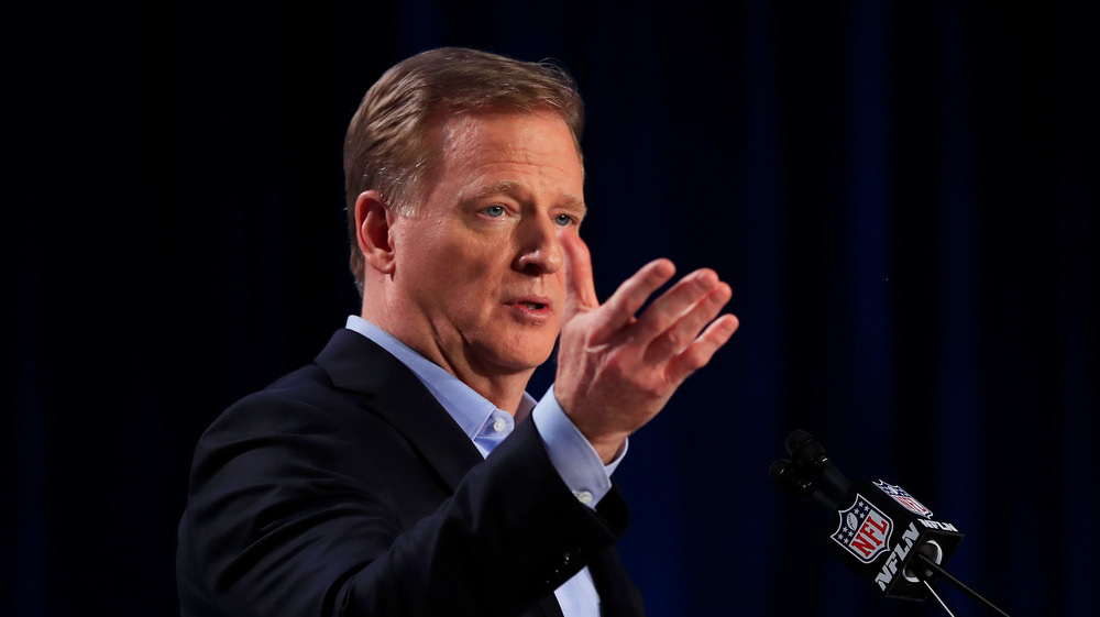 Roger Goodell with hand out