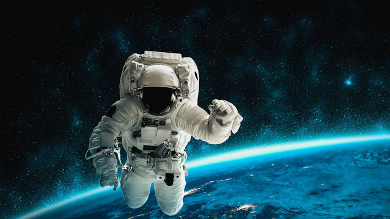Astronaut floating in space with Earth's curve in background