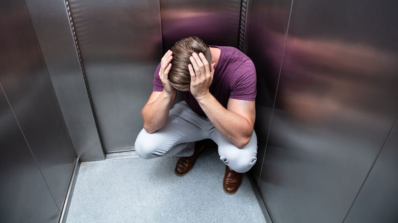 Man crouched in anxiety in elevator
