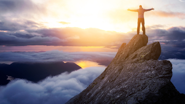 person standing on mountaintop arms spread
