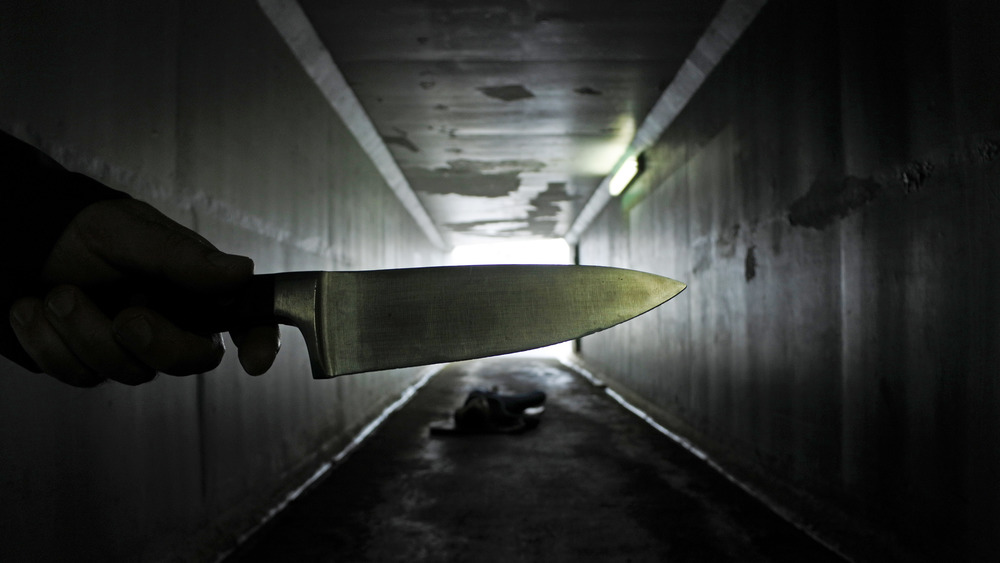Hand holding knife over body