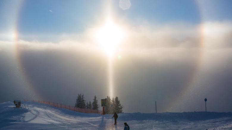 sun halo over skiers