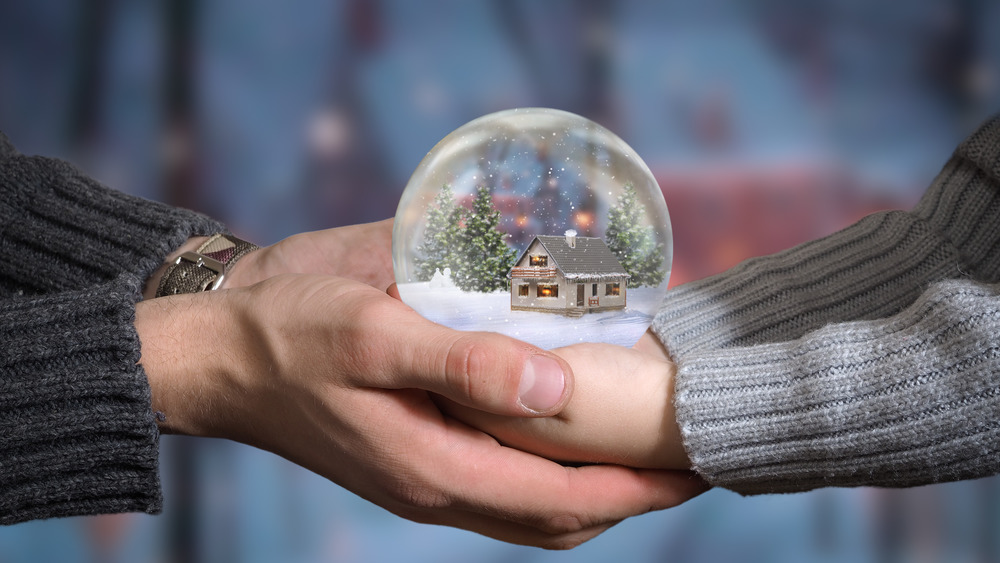 Adult hands and child hands holding a snow globe