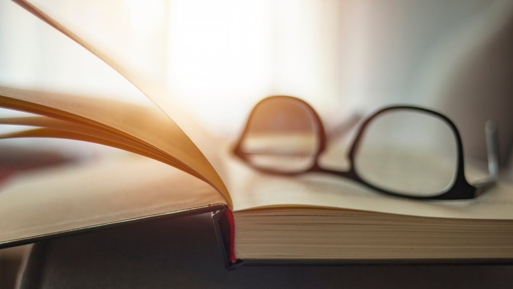 A pair of glasses sits on top of a book