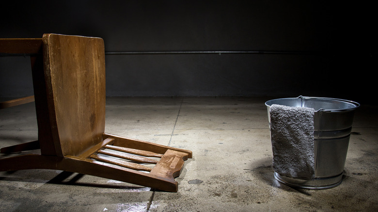 chair and bucket in stark room