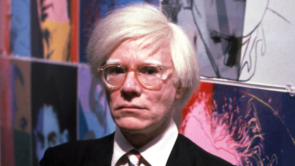 Andy Warhol with his paintings