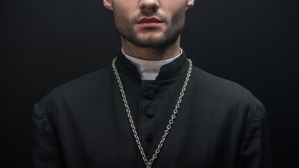 Ominous priest standing against dark background