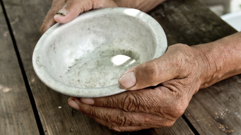 hand with empty bowl